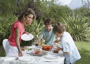 Mother and two sons (6-11) laying dinner table in garden